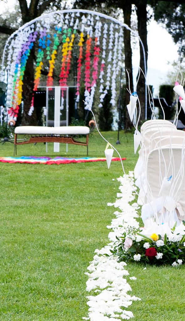 backdrop bianco e arcobaleno con coni di tulle in giardino per cerimonia civile